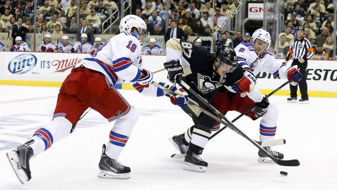 Rangers defensemen Marc Staal, left, and Anton Stralman, right, put the squeeze on Penguins star Sidney Crosby during Game 1 on Friday night.