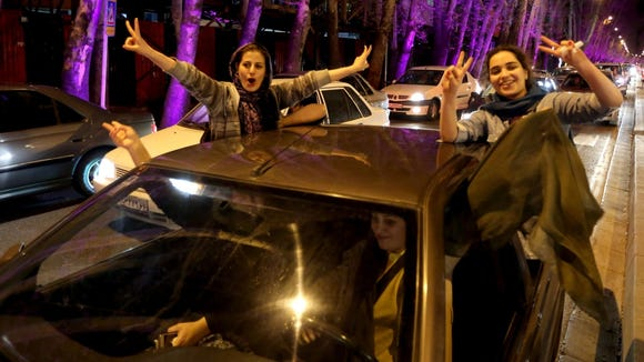 """Women flash the """"V for Victory"""" sign in Tehran after the announcement of a nuclear deal between Iran and the United States. (Atta Kenare/Agence France-Presse)"""