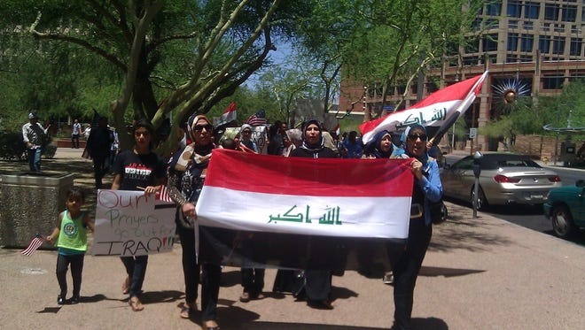 Members of the Iraqi community in metro Phoenix marched Wednesday to ask for more U.S. action to help curb militant violence in that native country.