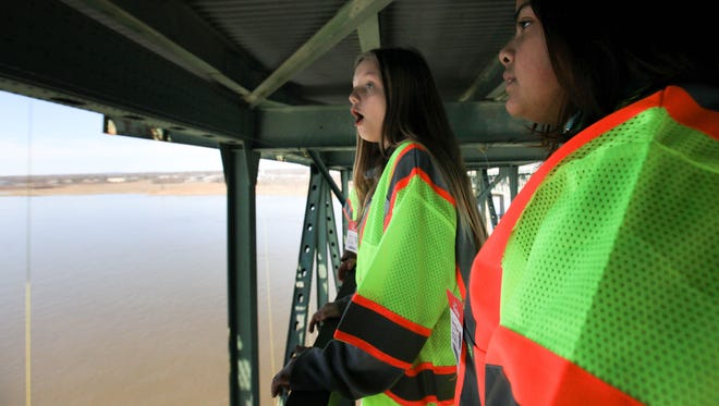 Kayla Reynolds, left, and Zoila Morales look out across the Delaware River from a catwalk on the underside of the Delaware Memorial Bridge, approximately 175 feet above the water.