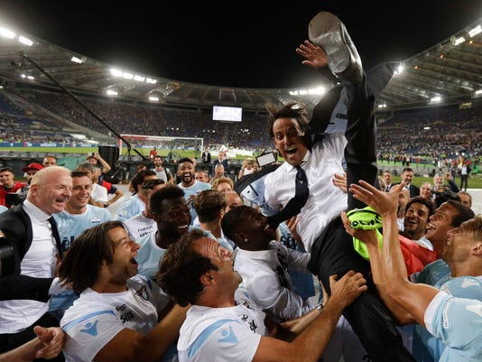 Lazio coach Simone Inzaghi is cheered by his players at the end of the Italian Super Cup final match between Lazio and Juventus at Rome's Olympic stadium, Sunday, Aug. 13, 2017. Lazio won 3-2. (AP Photo/Gregorio Borgia)