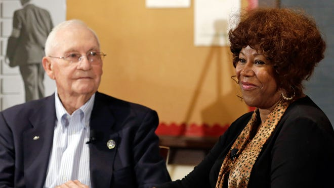 In this Sept. 2013 file photo, Ruby Bridges, who integrated Louisiana schools in 1960 under escort from U.S. Marshals, meets with Charles Burks, who was one of those marshals, at the Indianapolis Children's Museum in Indianapolis. On Friday, Nov. 14, 54 years later to the day when she first walked up the steps to William Frantz Elementary School, Bridges commemorated the event with the unveiling of a statue in her likeness on the campus.