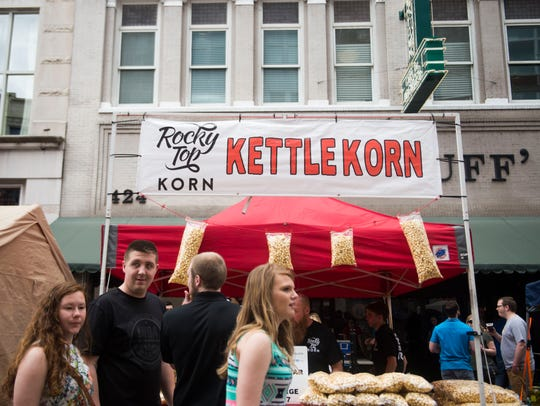 Attendees walk past a kettle corn booth at the 17th