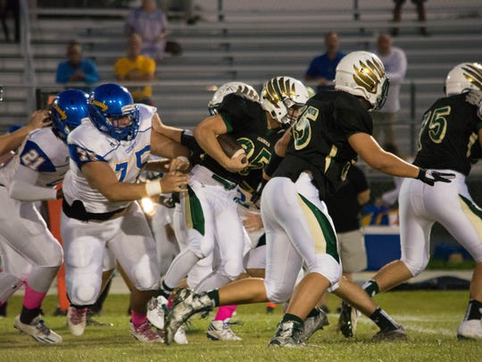 Viera High's Mike Vega (25) slips through the line in the first game against Martin County this season.
