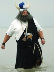 Dressed as the Marysville High School Viking mascot Dave Poulsen, of Smiths Creek, makes his way back to the shore during the annual Kiwanis Polar Bear Plunge at Lakeside Beach.