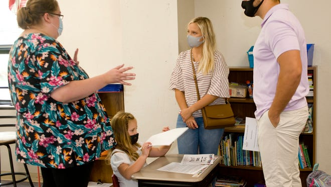 BriAnne Castellanteta, a kindergarten teacher at Regina Coeli Elementery School, answers questions and explains protocol for the upcoming school year to Kennedy Griest and her fiancee, Carson Kovath, as Adalyn Griest, 5, arranges papers at her desk Sunday during a dropoff/paperwork event at the school.