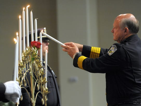 Alamance County Sheriff Terry S. Johnson lights a candle