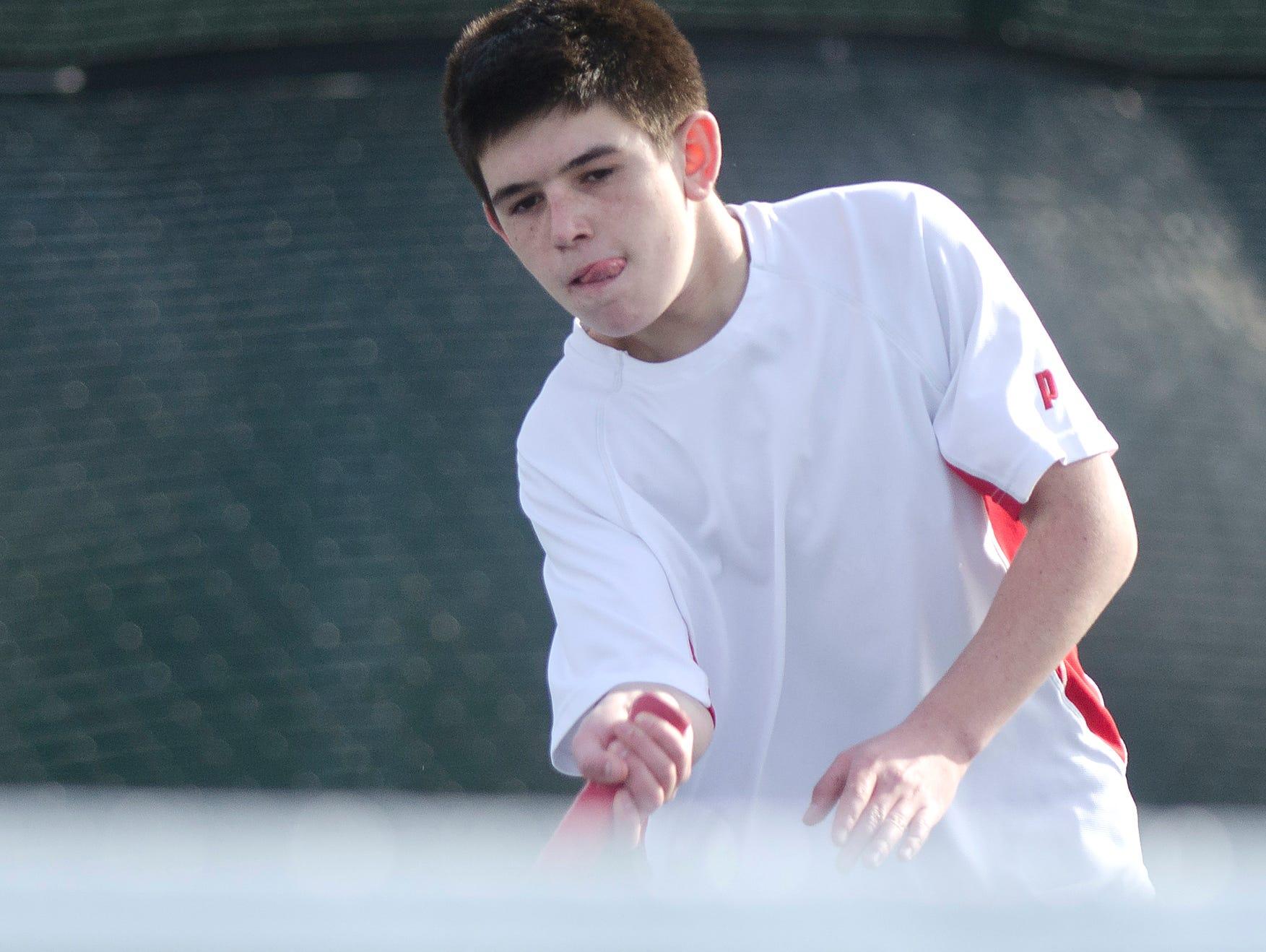 Champlain Valley doubles player David Huber returns a shot during a match last season.