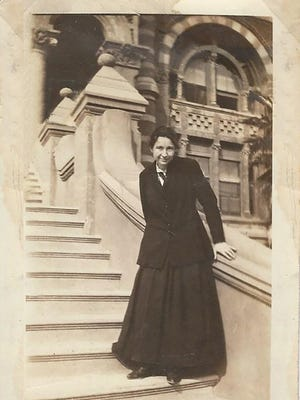 Anna Bowie standing on the steps of Old Red, the first University of Texas Medical Branch building built in 1891 and named for Ashbel Smith, a Republic of Texas diplomat and one of the founders of the University of Texas system.