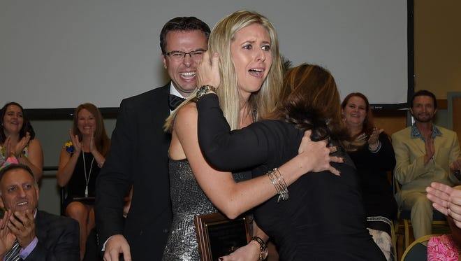 Ellise Ryan reacts as she is named Martin County School District teacher of the year at the awards ceremony Nov. 4. She hugged Kerrie Cuccurullo, a middle school teacher of the year candidate, as high school teacher of the year Charles Santos looked on.