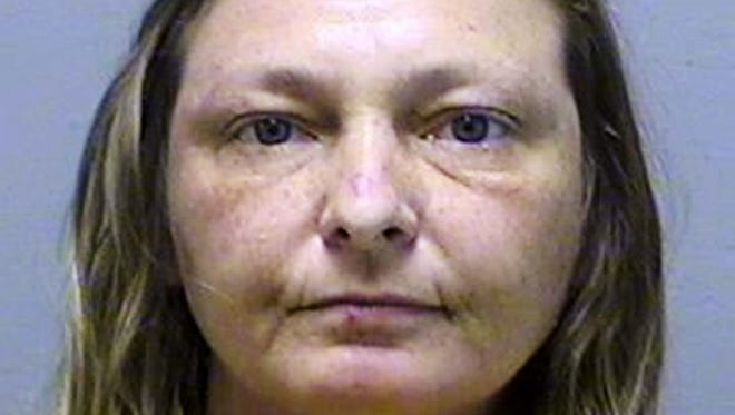 This file photo provided by the Genesee County Sheriff's Department in Flint, Mich., shows Lisa Corcoran, of Vienna Township, who is accused of stealing a handmade bench, flowers and other objects from local cemeteries that were later used to decorate her home. A judge in Flint sentenced Corcoran on Monday, July 24, 2017, to nine months in jail, with credit for 36 days already served. (Genesee County Sheriff's Department via AP, File)