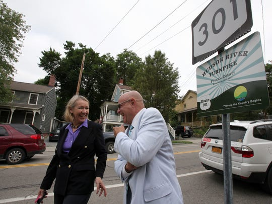 Director of Putnam County Tourism Libby Pataki and Putnam County Transportation Manager Vincent Tamagna laugh before the official unveiling of a sign in Cold Spring on June 18, 2012 for the newly named Hudson River Turnpike, also known as Route 301.