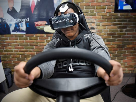 Abdiaziz Mohamed takes the wheel of a virtual reality simulator designed to illustrate the dangers of distracted driving Tuesday, May 10 at Apollo High School in St. Cloud.