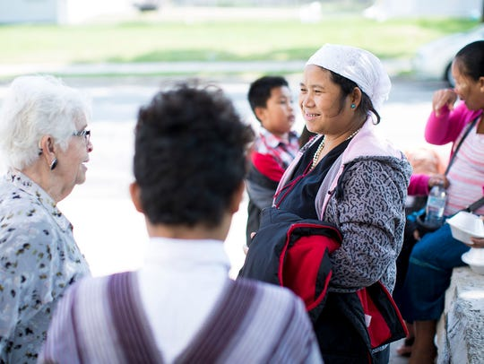 Ca Tri Na speaks with other parishioners outside St. Michael's Church Sept. 10, 2017, in Milwaukee. The church is attended by many refugees.