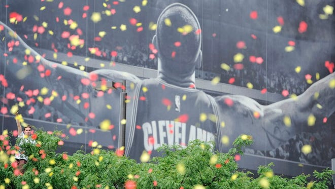 A fan sits atop a tree in front of the LeBron James mural during the Cleveland Cavaliers NBA championship parade in downtown Cleveland June 22, 2016