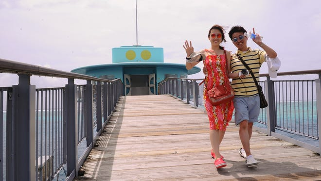 """Kwon Yongil, right, and and his wife, Jeon Yun Hee, wave to the camera as they walk away from the Fish Eye Marine Park underwater observation tower in Piti on Thursday, July 9. The couple, married in Korea on July 4, decided to spend their honeymoon in Guam. The Imagine Guam initiative on Thursday officially kicked off with its first panel discussion on how the community envisions the island 50 years from now. Part of the next step in the Imagine Guam initiative is the formation of 17 """"imagination teams,"""" with each team having a specific area of focus, including """"hospitality."""" Rick Cruz/PDN"""