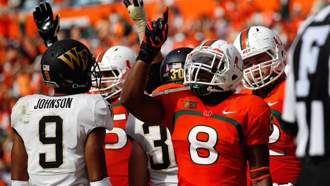 Miami Hurricanes running back Duke Johnson (8) reacts after scoring the game winning touchdown in the fourth quarter as Wake Forest Demon Deacons cornerback Kevin Johnson (9) looks on at Sun Life Stadium. Miami won 24-21.