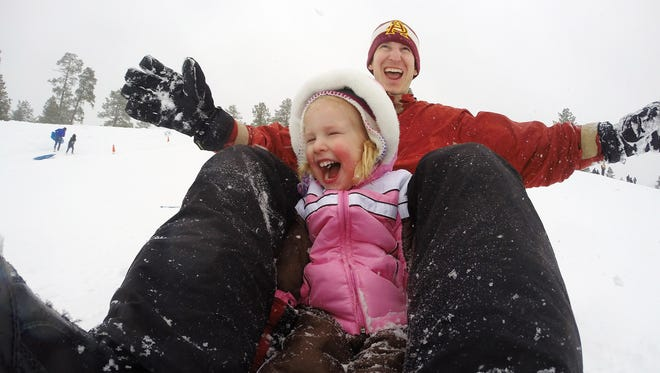Mark Walters, 33 from Phoenix and his daughter Alanna, 2, sled down a hill at Wing Mountain Snow Play Area north of Flagstaff January 22, 2017.