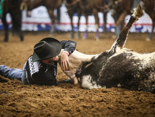 Jacob Talley wrestles a steer during the 11th performance