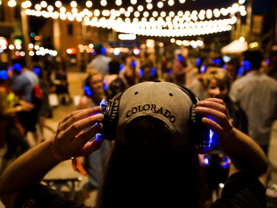 Sean Hall, known as DJ Wadada, puts on his headphones at the silent disco during FoCoMX on Friday, April 27, 2018, at Old Town Square in Fort Collins, Colo.