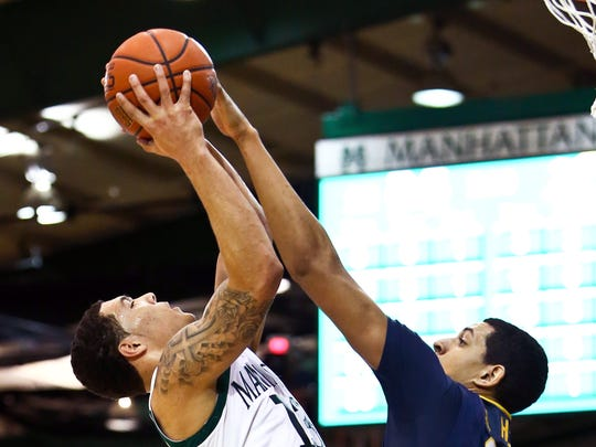 Manhattan's Emmy Andujar and Canisius' Jordan Heath battle for the rebound at Draddy Gymnasium during a 2013 game.