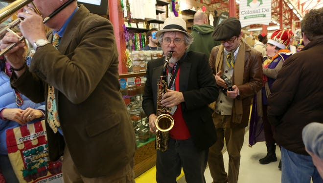 Members of the band Lagniappe lead the Mardi Gras parade through Findlay Market on Feb. 10, 2013.