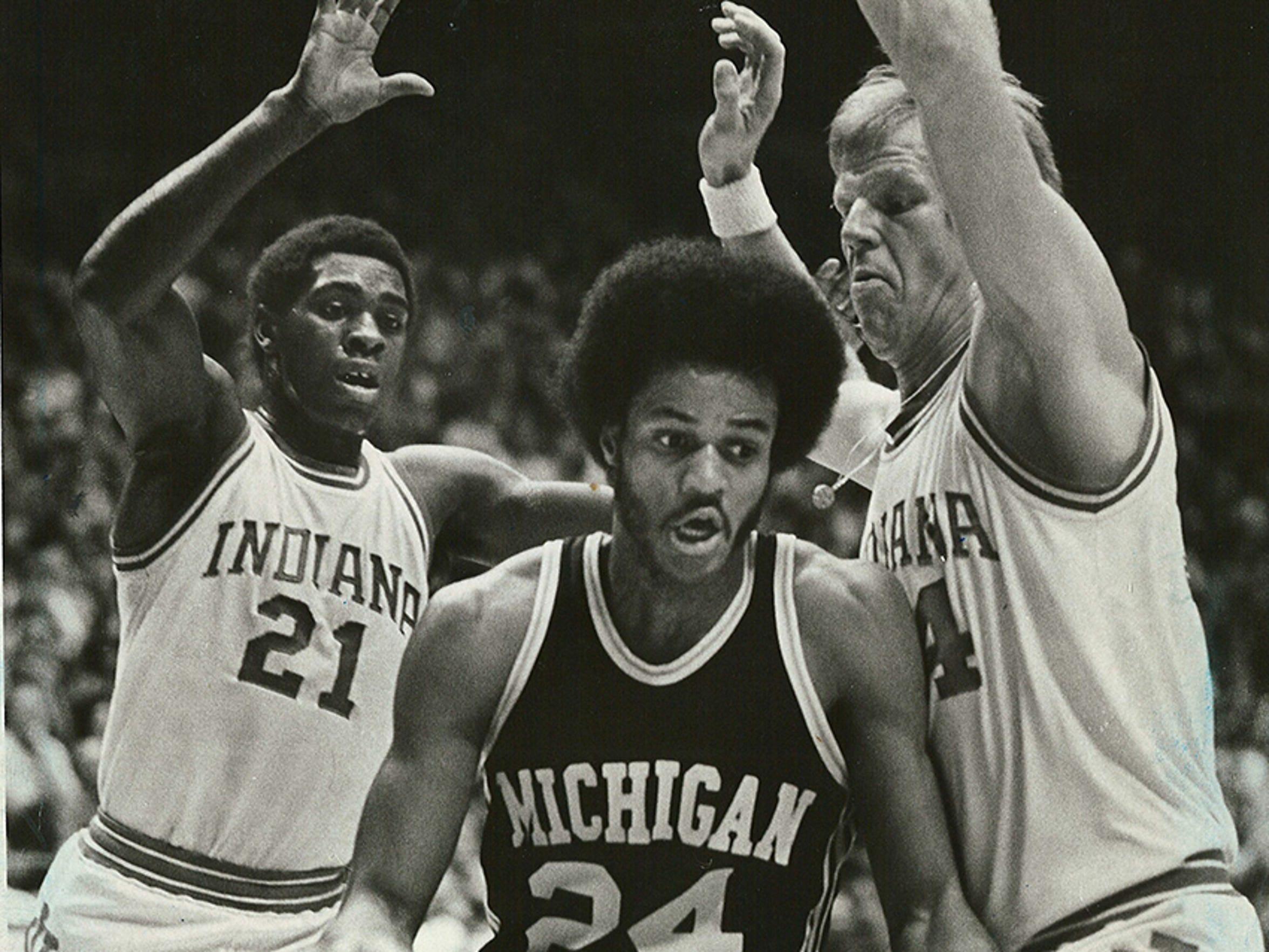 Quinn Buckner and Kent Benson stop Michigan's Rickey Green along the baseline, Feb. 7, 1976.