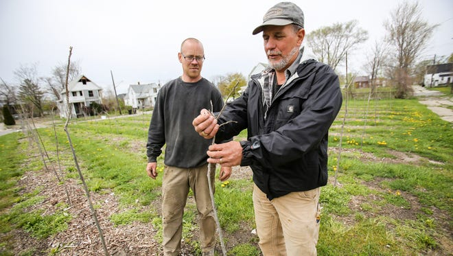 Mike Score, president of Hantz Farms, right, and Andy Williams, manager of Hantz Farms, walk through the neighborhood where Hantz Woodlands are located in Detroit on Wednesday, May 4, 2016.