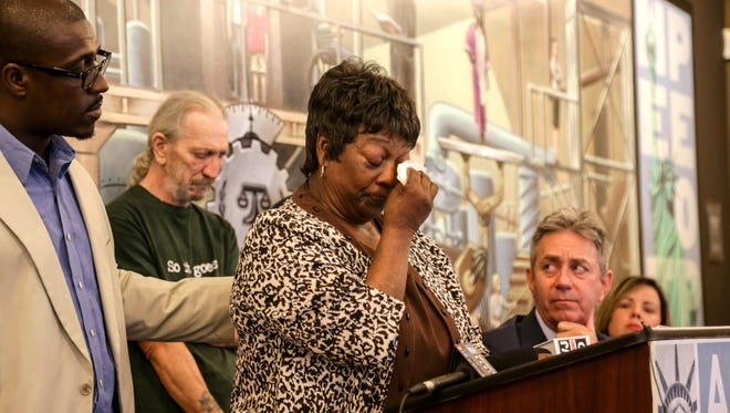 Detroit resident Julia Aikens, 67, of Detroit takes a moment to collect herself, with help from ACLU's Darrel Dawsey, as she speaks during a press conference held by the ACLU of Michigan, the NAACP Legal Defense and Educational Fund, Inc. and lawyers from Covington & Burling LLP announcing the filing of a class-action lawsuit against the Wayne County Treasurer, Wayne County and the city of Detroit to challenge legal, racially discriminatory tax foreclosures that have affected African-American homeowners in recent years at ACLU offices in Detroit on Wednesday, July 13, 2016.