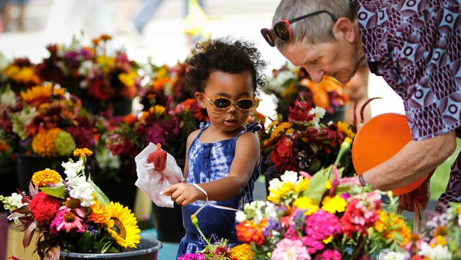 Kamisa Buckley, 2, of East Lansing, helps her grandmother Monika Brosi-Dembele (visiting from Germany) pick out a bouquet of flowers July 28, 2016, at the Capitol Farmers Market on the Capitol lawn.