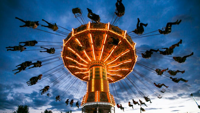 The Wave Swinger sends riders flying above the crowds at the Oregon State Fair on Sunday, Sept. 4, 2016. The ride formerly operated at Michael Jackson's Neverland Ranch. The 151st annual State Fair saw increased revenue and attendance, and carnival rides were operated by newcomers Rainier Amusements.