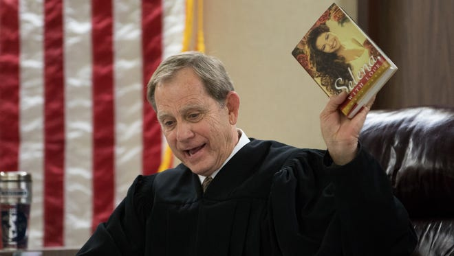 """Judge Guy Williams holds up a copy of Chris Perez's book """"To Selena, with Love"""" during a hearing for a civil lawsuit filed by Selena's father Abraham Quintanilla Jr. regarding Perez's plans for a TV series based on the book in the 148th district court in the  Nueces County Courthouse's on Friday, Feb. 17, 2017."""