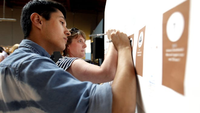 Elias Garza, 20, of Frankfort, Ind., and Jessica Barnes, 33, of Lafayette, sign the Indiana timeline for when their families arrived in the state, at the ALL-IN digital competition launch party at The Speak Easy in Indianapolis on Tuesday, June 24, 2014. The program, by Indiana Humanities, encourages Hoosiers to learn more about Indiana, try new things and share their progress on social media.