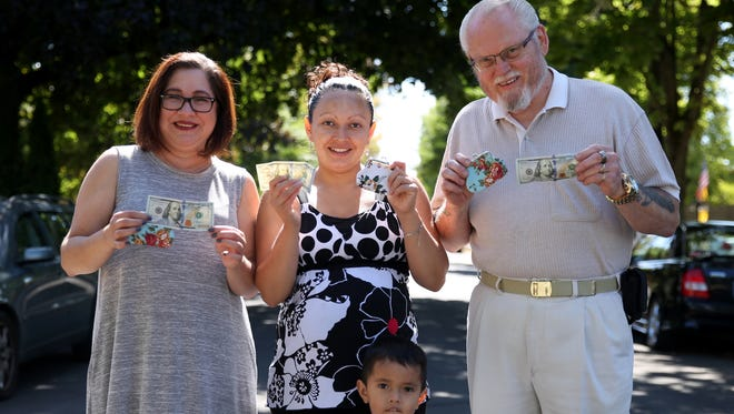 Neighbors, from left, Marcela Miles, 55, Maria Gaytan, 33, her son Angel Pacheco, 3, and Jim Mogle, 74, show off coin purses and $100 bills left by Salem philanthropist 'Benny' in Salem on Wednesday, Sept. 13, 2017.