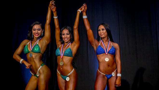 Bikini division winners, from left, Camerin Mendiola, second place, Victoria Espaldon, first place, and Keisha Raras, third place, in the Michelob Ultra Bodybuilding and Fitness Championships, hosted by the Guam National Physique Federation at the Sheraton Laguna Guam Resort on Nov. 17.
