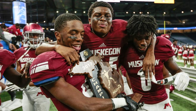 From left, Muskegon players Marvin Harwell Jr. (4), Ka'Marius Baker-Matthews (25), and Clinton Jefferson Jr. (6) celebrate after Muskegon's 28-10 win in the Division 3 state title game on Saturday, Nov. 25, 2017, at Ford Field.