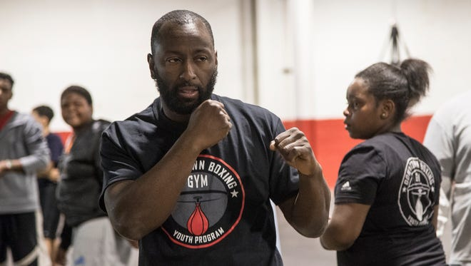 Khali Sweeney, founder and CEO of Downtown Boxing Gym, center, demonstrates during a training session at the Downtown Boxing Gym in Detroit, Friday, December 8, 2017.