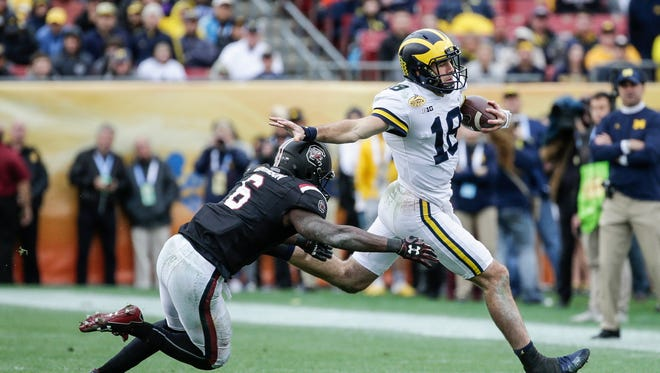 Michigan Wolverines quarterback Brandon Peters is chased by South Carolina linebacker T.J. Brunson during the first half of the Outback Bowl at Raymond James Stadium in Tampa, Fla., Monday, Jan. 1, 2018.