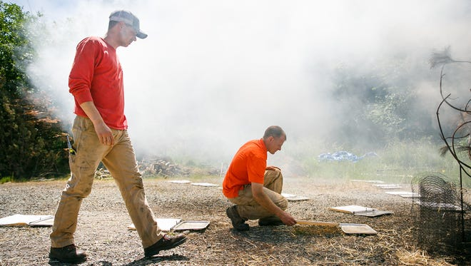 Oregon State masters student Tyler Hudson, left, and assistant professor David Blunck, right, look at fire-resistant fabric to see how many embers resulted from setting fire to a small stand of ponderosa pine for an experiment on Saturday, June 2, 2018, in Albany. Hudson's masters thesis researches ember dispersal from forest fires.