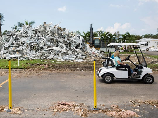 Residents drive by an aluminum pile in Naples Estates, a mobile home community off of Rattlesnake Hammock Road, on Thursday, Sept. 14, 2017, in East Naples, Fla. FEMA set up shop in the community, registering 250-plus residents in the surrounding area.