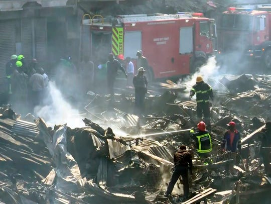 In this image from TV, a fire fighter damps down the