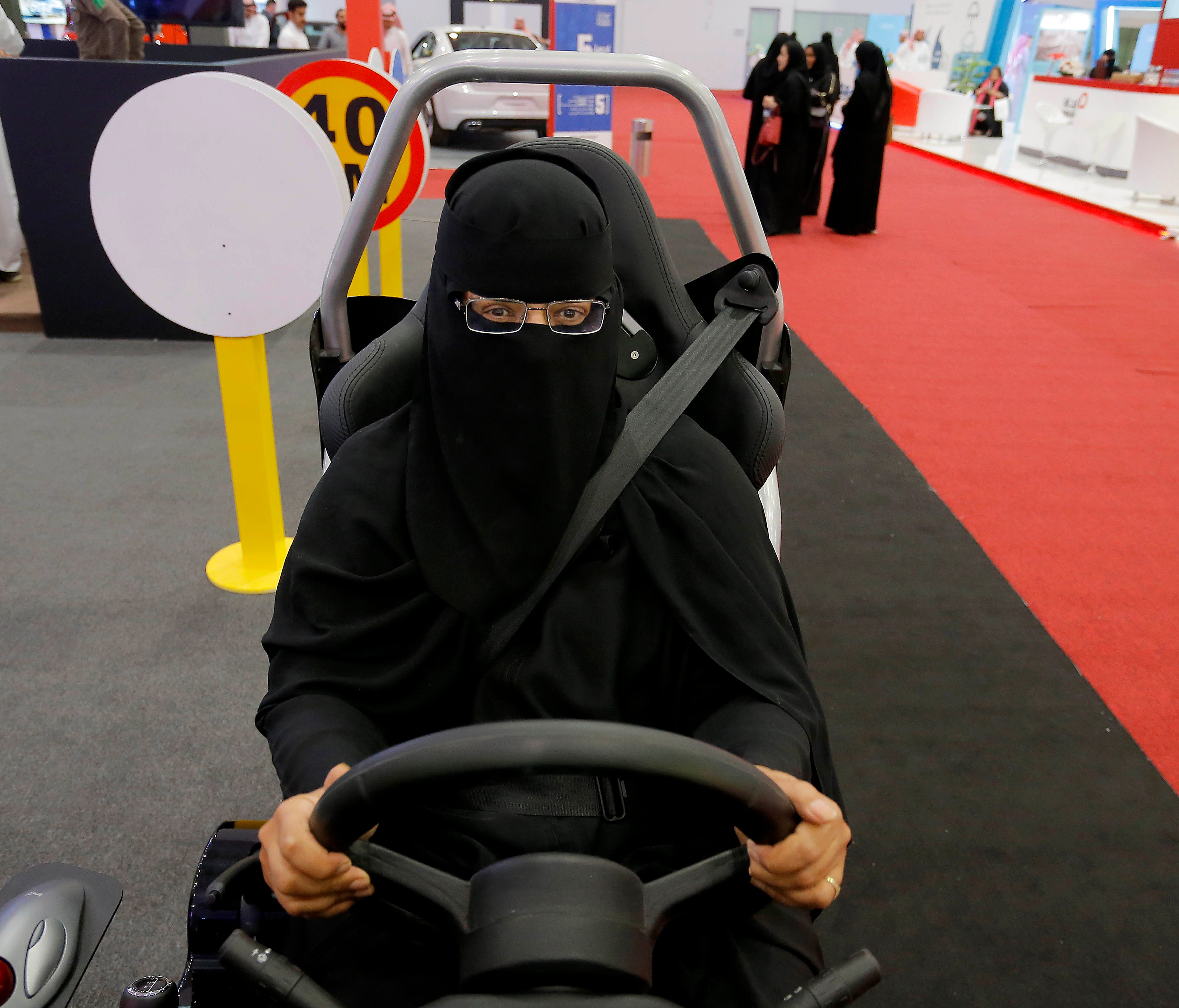 A women sits in a driving simulator during a car show only for women in Riyadh, Saudi Arabia,