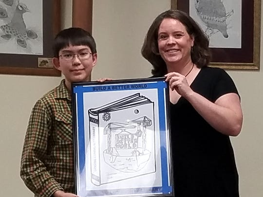 Library Trustee Ami Stallone presents Thomas Wells with a poster-sized version of his winning logo for the Lansing Community Library's Summer Reading Program. Thomas' work was chosen from among 63 entries. On April 24, Lansing voters approved the library's budget for 2018, and elected Kathy McDonald, Darcy Rigdon, and Deborah Huber-Wang as trustees.