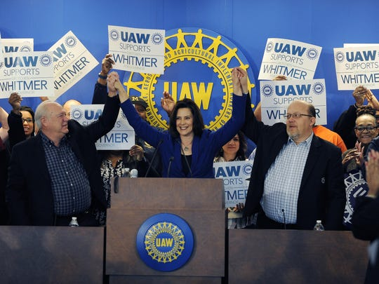 Then-Democratic candidate for governor Gretchen Whitmer raises her hands with then-UAW President Dennis Williams, left, and Frank Stuglin, Assistant Director of Region 1, after accepting the endorsement from the UAW this morning.