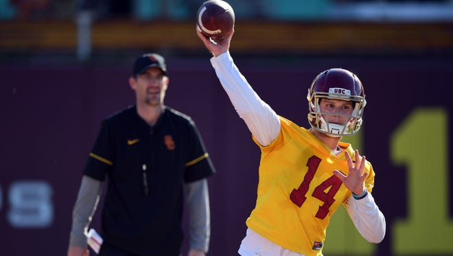 Southern California Trojans quarterback Sam Darnold (14) throws a pass under supervision of quarterbacks coach Tyson Helton during spring practice at Howard Jones Field.
