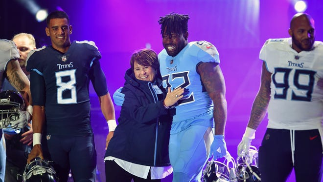 Tennessee Titans tight end Delanie Walker (82) hugs Titans owner Amy Adams Strunk after the Titans revealed their new uniform during a block party downtown Nashville on Wednesday, April 4, 2018.