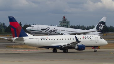A Delta Connection flight is seen within view of an Alaska Airlines flight in Seattle in June 2014.