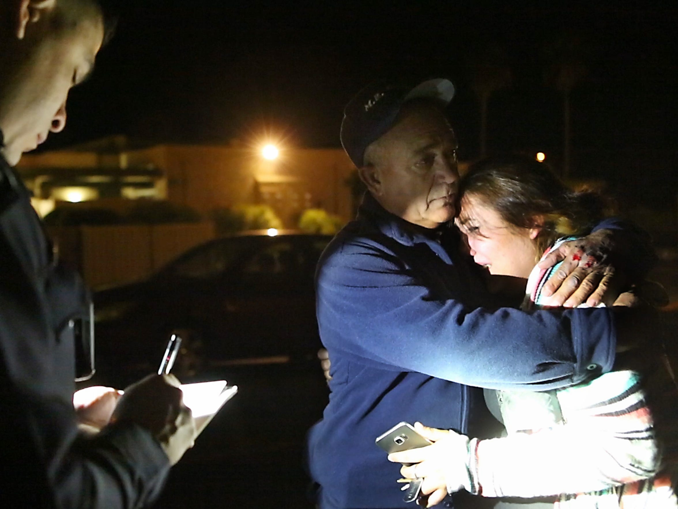Officer Adam Perez takes down a report as an uncle comforts his niece in Desert Hot Springs.