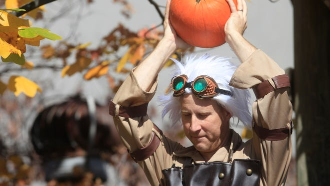 Troy Ganser, the director of the T.A.G. Art Company throws pumpkins from the railing of a tree house Saturday afternoon during a pumpkin smash at the Muncie Children's Museum. The group dressed as characters for the museum's Halloween Extravaganza where kids could meet characters, get their faces painted and more.