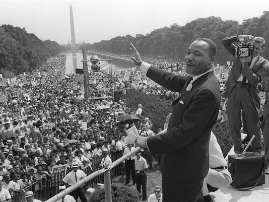 The civil rights leader Martin Luther KIng (C) wav